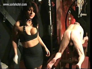 Dirty slave with his nipples pierced bends over and is spanked on his ass by beautiful mistress